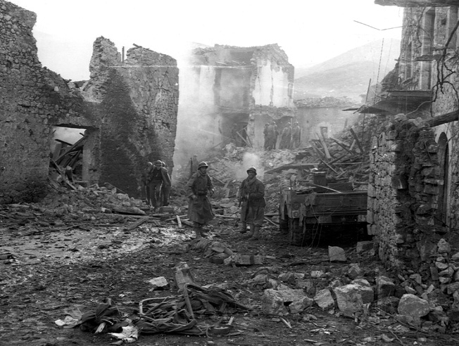 As the Italian Campaign wore on, the Luftwaffe appeared in force on fewer and fewer occasions. Here, however, debris still smolders in the streets of a town bombed and strafed by German aircraft moments before.