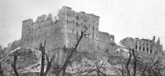 The ruins of the abbey of Monte Cassino bear mute testimony to the ferocity of the fighting that swirled around the ancient structure. Combat engineers have cleared a path through a possible minefield, marked by tape, in the lower center of the photograph.