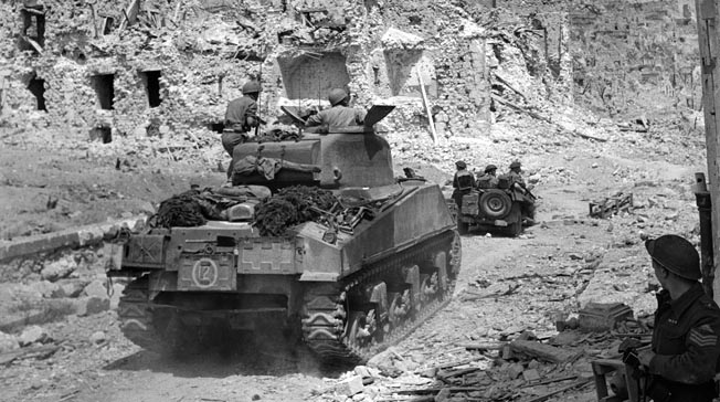 Operating with an American jeep and Sherman tank, elements of the New Zealand 4th Armoured Brigade move through the rubble of Cassino, May 18, 1944. The total destruction of the town inhibited the Allies' progress through it.