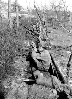 Near the banks of the Rapido River, American soldiers seek cover behind a thicket of brush and barbed wire on February 7, 1944. The ill-fated attempt by elements of the 36th Infantry Division to cross the Rapido was one of the war's most regrettable tactical reverses.