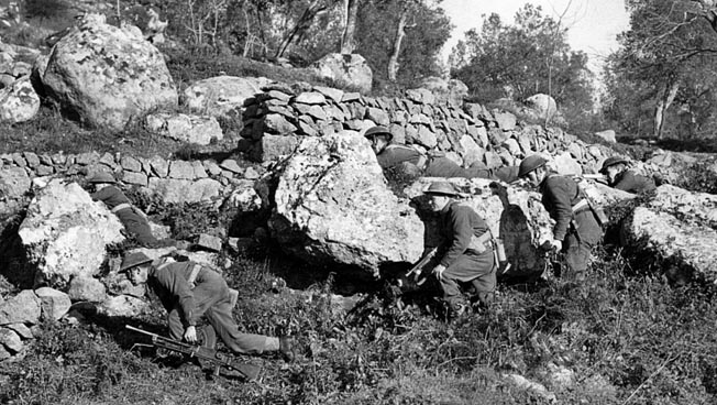 Advancing with Bren guns, British soldiers use the cover of a stone wall on a terraced hillside to advance against German positions near the town of Cassino, January 1944. It took the Allies four major assaults to finally secure Monastery Hill.