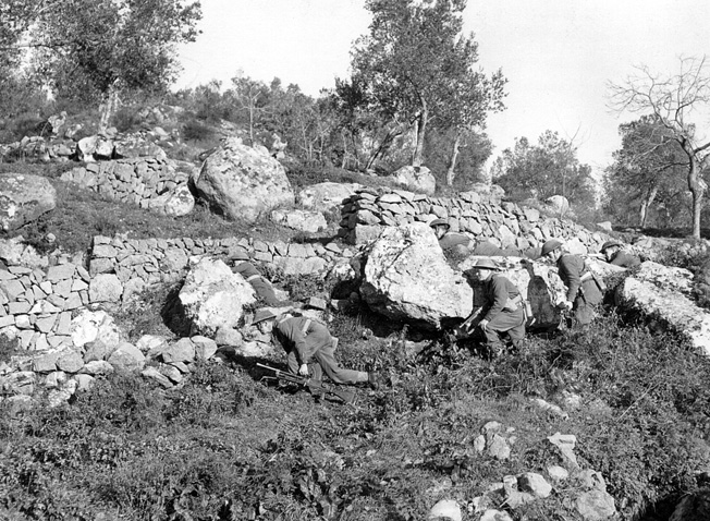 Carrying their standard-issue Bren guns, British soldiers use the cover of a stone wall to advance against German positions near the town of Cassino. The Allies eventually attempted four times to take the ruins of the Benedictine abbey above the town.