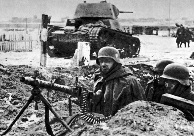 With a knocked-out Soviet tank behind them, a German MG-34 machine-gun crew watches for any sign of an enemy attack.
