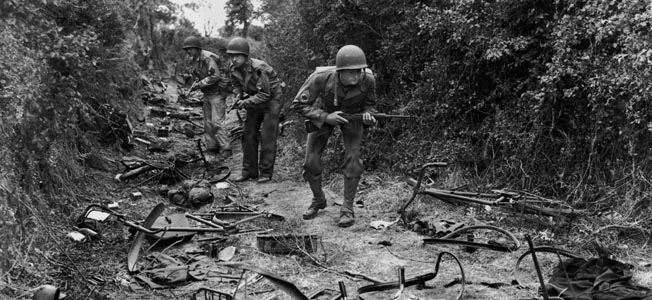 27th June 1944:  American troops advancing through a wood near Valognes, on the Cherbourg front. The track is littered with parts of bicyles and ironmongery.  (Photo by Fred Ramage/Keystone/Getty Images)