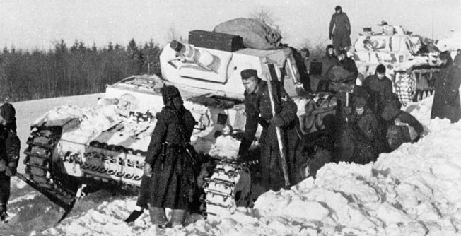 Being whitewashed to blend in with the terrain did not spare this German Pzkpfw IV Ausf. D with 75mm cannon from becoming immobilized in the snow. Troops use picks and shovels to try and free it. Much German equipment was simply abandoned on the battlefield.