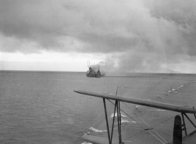 In a photograph taken from the deck of the USS Chicago, the Australian cruiser Canberra  lists to starboard and belches smoke as a destroyer pulls alongside to rescue crewmen.