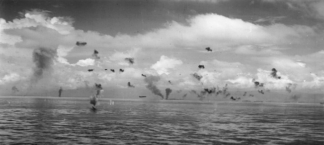 On August 8, 1942, a photographer aboard the Chicago captured this image of Japanese torpedo planes attacking American ships off of Tulagi in the Solomons. One plane streaks toward its target while two other are ablaze and antiaircraft fire dots the sky.