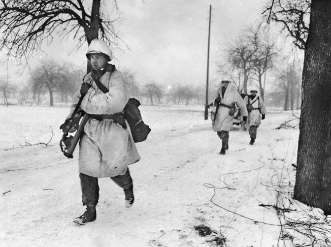 Camouflaged for winter fighting, American soldiers of the 15th Infantry Regiment advance along a country road in the Colmar area.