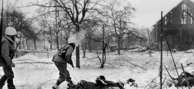 U.S. troops advance cautiously past the bodies of several dead German soldiers during combat on the outskirts of Jebsheim.