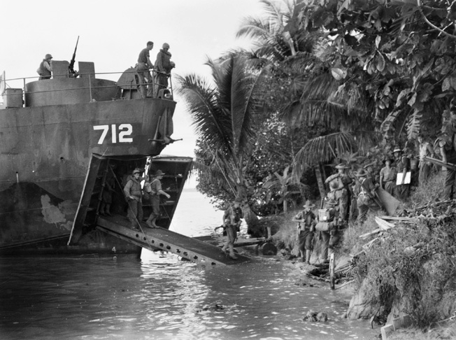 Pilling out of a landing craft unopposed at Sadau Island, Borneo, on April 30, 1945, troopers of 2/4 Commando familiarize themselves with their surroundings. No resistance from the Japanese was encountered on the island, and the Australians suffered no casualties.