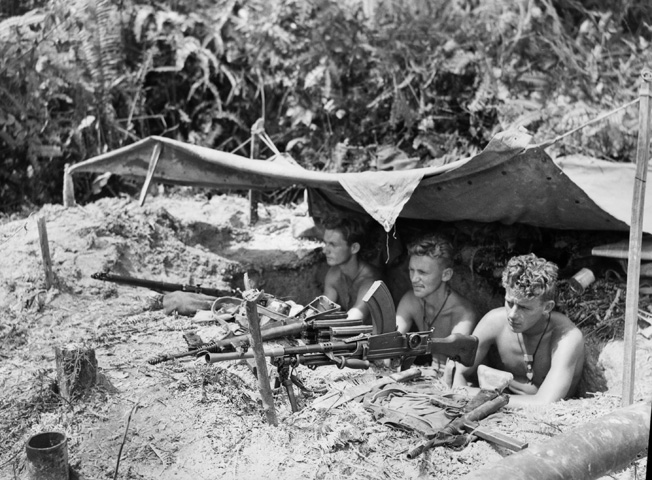 Manning a Bren gun position along the forward line of C Troop, 2/4 Commando Squadron covering an area known as Snags Track, troopers McGowan, Sherring, and McDonald cast a wary eye toward Japanese positions. These Australian commandos were ashore near Tarakan, Borneo, on May 13, 1945.