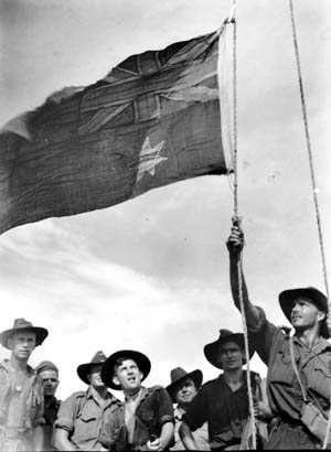Lieutenant K. McKitrick hoists the Australian flag on Sadau Island, Borneo, April 30, 1945. The battle hardened soldiers of the 2/4 Commando Squadron look on during the impromptu ceremony.
