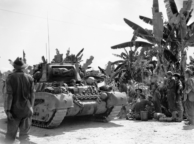 On May 2, 1945, a tank attached to 13 Troop, 2/9 Armed Regiment advances toward Horseshoe Knoll during the fighting for Tarakan Hill and neighboring oil fields. Fatigued members of 2/4 Commando Squadron press forward along with the armor in support of D Company, 2/23 Infantry Battalion.