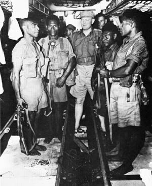 Waiting for the signal to board a small rubber craft for landing on Japanese-held New Guinea, an Australian intelligence agent and four native comrades pass the time aboard the submarine USS Dace.