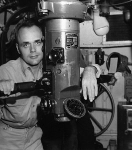 Commander Bladen D. Claggett, skipper of the submarine USS Dace, poses with his periscope aboard the vessel in September 1945.