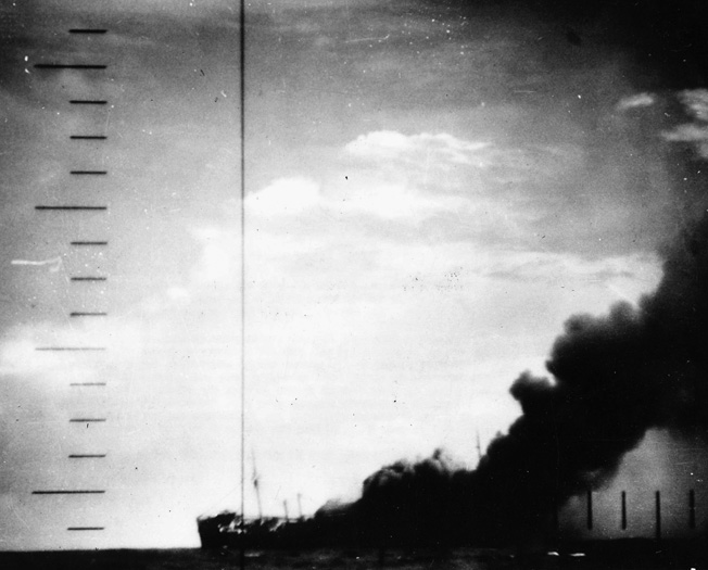 Seen through the pariscope of the U.S. Navy submarine that has just successfully attacked it, a stricken Japanese warship lists to port and belches a heavy cloud of black smoke before plunging to the bottom of the Pacific Ocean.