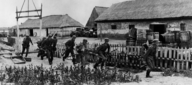 Advancing through a small Russian village near Kerch, German soldiers look to secure the adjacent buildings. The Red Army offensive that began with high hopes in the Crimea in the winter of 1941 soon came to grief as German commanders responded with counterattacks.