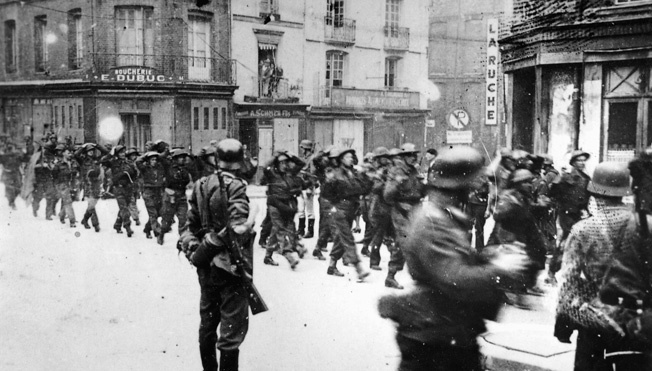 As their German captors look on, British POWs are marched down a street shortly after the Dieppe landings of August 19, 1942.