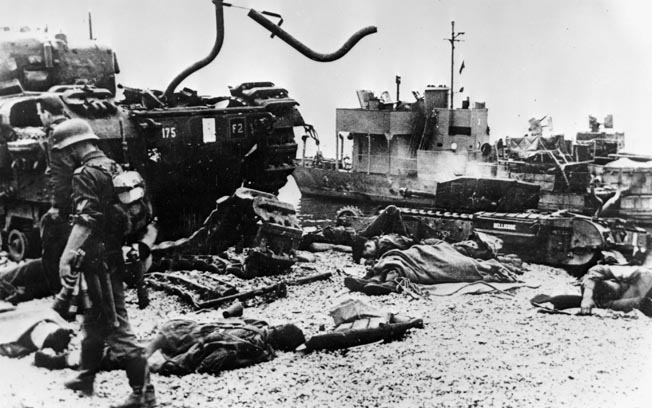 A German soldier, carrying stick grenades, surveys the carnage on the beach shortly after the battle. Few of the 24 British tanks that landed made it off the beach, and all were lost.