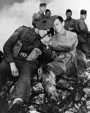 A U.S. Army Ranger offers a light to an English commando during training for the upcoming raid on Dieppe.