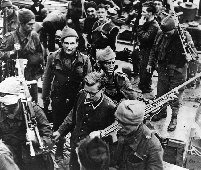 A group of Canadian soldiers captured on film shortly after the raid with a German POW.