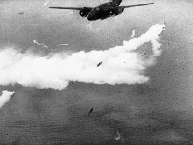 As British naval units lay a smokescreen far below, RAF bombers release their payload over Dieppe.