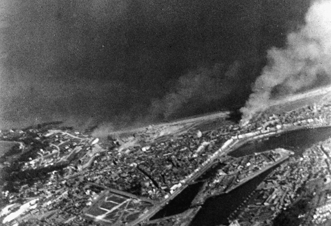 A large fire burns and the smoke of battle engulfs the area in this shot taken by an RAF film unit flying over the target area.
