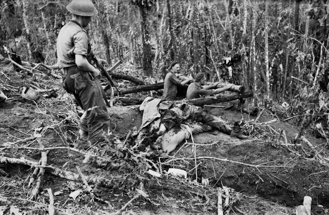In November 1944, Australian soldiers view the bodies of Japanese troops killed on Bougainville.