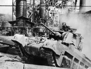 A tank of the Australian 7th Division traverses difficult terrain on the island of Borneo as a destroyed oil refinery looms in the background.