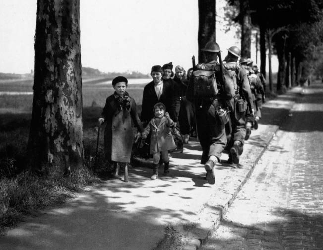 A British soldier moves to the battlefront past refugees headed the other way.