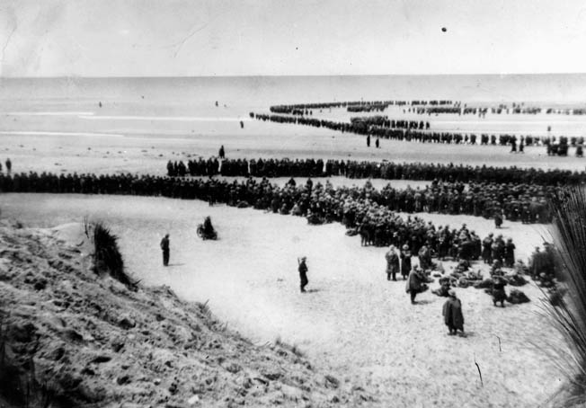 "A line of evacuees snakes through from the beach into the surf at Dunkirk. The British pressed 300 ""little ships"" into service to help rescue the thousands awaiting evacuation."