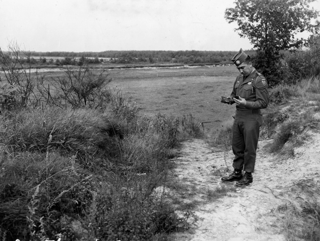 In a photo taken on September 17, 1956, Pfc. Garcia, a former member of the 101st Airborne Division, stands a few yards from where trooper Joe Mann was killed. Garcia is holding a charred German rifle butt and an ammunition clip from an American M-1 rifle.
