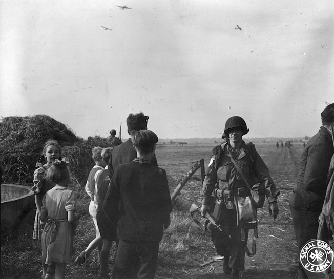 With gliders still visible in the sky, paratroopers of the 101st Airborne Division complete a picture perfect parachute drop into the Netherlands during the opening phase of Operation Market-Garden in September 1944.