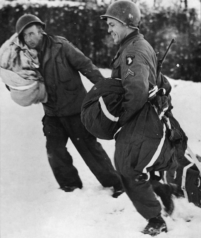 Defending Bastogne during bitter winter fighting, troopers of the 101st Airborne Division recover a canister of medical supplies which has been airdropped to the surrounded soldiers. the 101st held the crossroads town during the Battle of the Bulge until relieved by the 4th Armored Division.