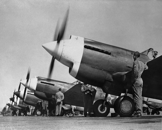 """08 Dec 1941, California, USA --- Original caption: """"Props"""" start turning as ground crews from the fighting 20th Pursuit Group stand by at their base, Hamilton Field. This outfit, which has just returned from three months fighting in the Louisiana and the Carolina wars, may soon see some real action in the Japanese-United States conflict. --- Image by © Bettmann/CORBIS"""