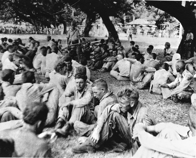 Starving, thirsty, and subjected to barbarous treatment by their Japanese captors, American personnel captured on the Bataan Peninsula rest briefly under the watchful eye of Japanese guards during the infamous Bataan Death March.