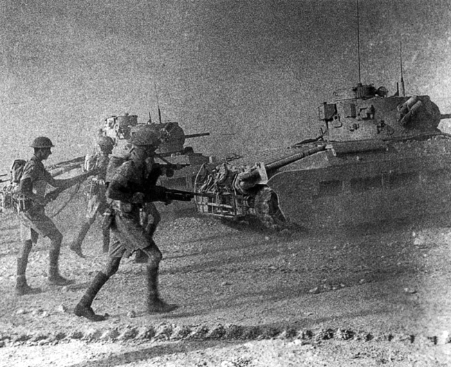 This image taken in July 1942, shortly after the German advance across the North African desert had been checked during the first battle of El Alamein, shows British soldiers advancing during a training exercise intended to improve coordination between infantry and armor.