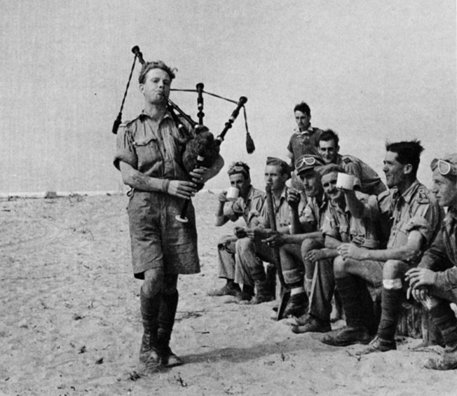 During a lull in the desert fighting, a bagpiper entertains British soldiers with an impromptu concert.