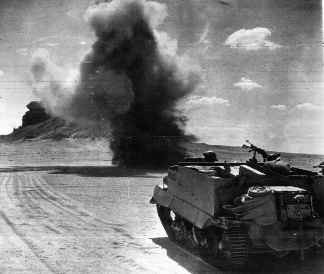 Patrolling in their Bren gun carrier, a group of British soldiers comes under fire from German artillery positioned beyond the desert horizon.