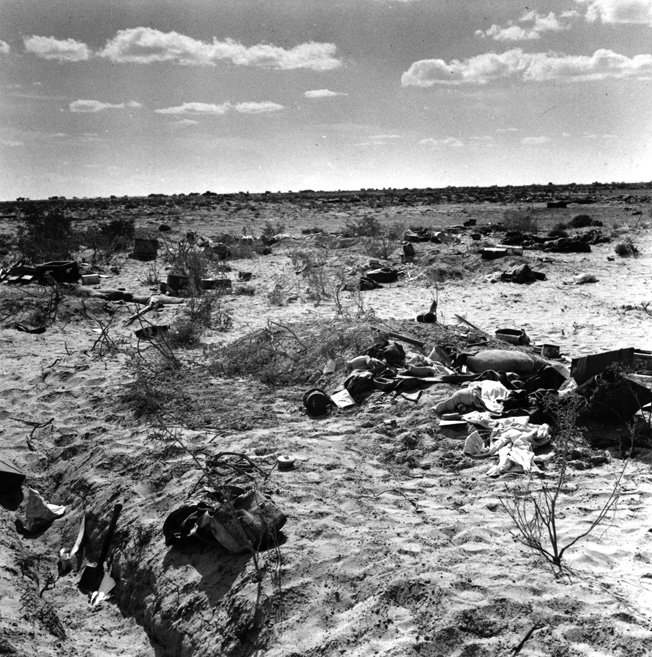 Dead Germans and their personal effects lie strewn across a scarred landscape following the capture of their position by British troops during the early stages of the Battle of El Alamein.