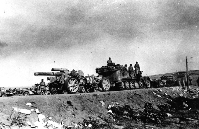 Its carriage towed by a half-track, a heavy German artillery weapon is moved into position during the first phase of the fighting at El Alamein.