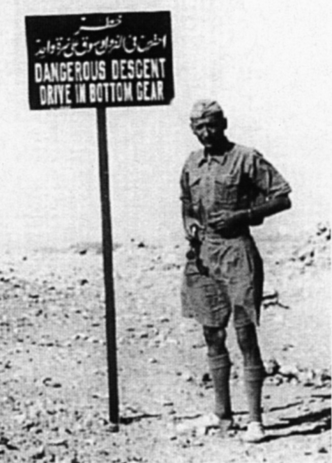 Almasy poses beside a warning sign (which he removed in a minor act of sabotage) at Yaboa Pass, 50 kilometers (31 miles) beyond Kharga oasis, before proceeding several hours more to the rim of the Egyptian plateau along the Nile Valley above Assiut, where he dropped off two spies of Operation Condor.