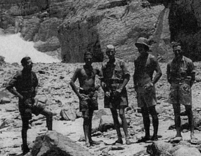 "The Operation Salaam team poses at the mouth of Wadi Sura in the western escarpment of the Gilif Kebir. Almasy is at center wearing an overseas cap; Egyptian-born principal spy Johann (""John"") Eppler is on his right. The team paused to examine the ""Cave of Swimmers,"" one of several prehistoric painted caves that Almasy discovered in 1930-1933 in the Gilif and at Jebel U'weinat."