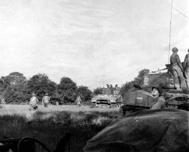 American infantry and Sherman tanks advance across an open field in Normandy. The soldier at right is watching Allied warplanes coming in for a strafing run.