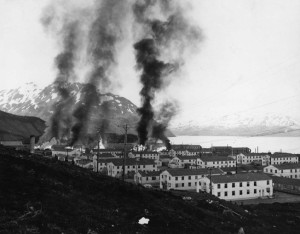 Following a Japanese air raid on the U.S. base at Dutch Harbor in the Aleutians, June 3, 1942, smoke billows from Fort Mears. This photograph was taken from the installation's water tower a landmark that could be seen from some distance.