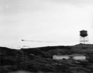 Trailing smoke, a stricken Japanese aircraft appears headed for a crash during the raid on Dutch Harbor. The opening shots of the Battle of Midway were fired in the Aleutians.