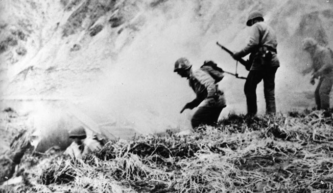 An American combat patrol goes in search of Japanese holed up in dugouts on Attu, May 1943.
