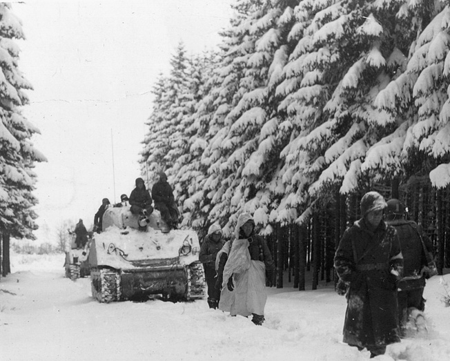 Cold and frostbitten, members of the 82nd Airborne march with tanks of the 2nd Armored Divi- sion and advance into the northern sector of the Bulge.