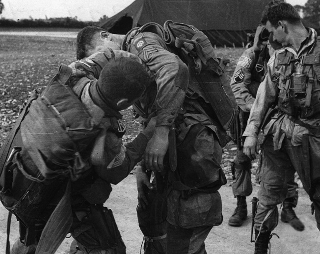 Paratroopers of the 82nd Airborne strap on their gear before their flight from England to Holland.