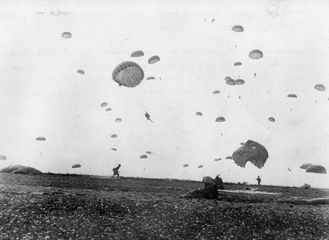 A lone paratrooper makes his way across a field to the assembly area as his comrades make their way to the ground.